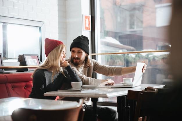 Vista lateral do lindo casal com laptop