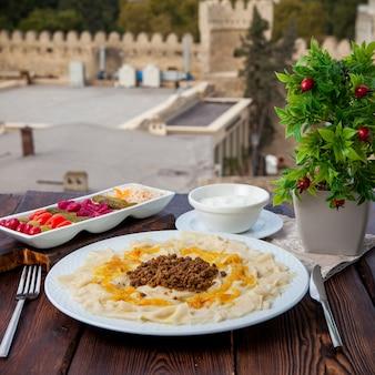 Vista lateral do macarrão caucasiano guru khingal do azerbaijão com carne picada frita e cebola com molho de creme de leite e picles com vista da cidade