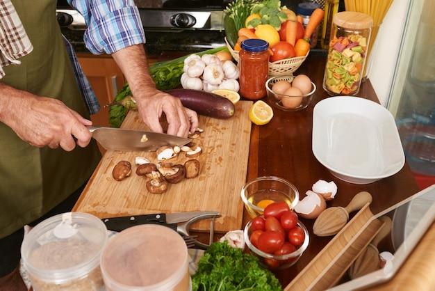 Vista lateral do macho mãos cortando cogumelos para o prato orgânico