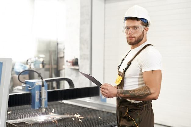 Vista lateral do mecânico forte no trabalho de proteção de óculos