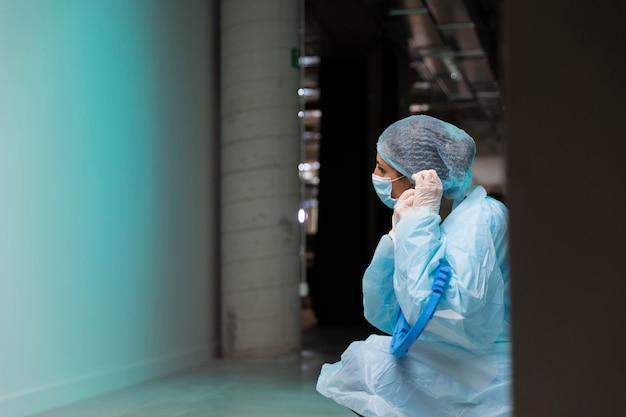 Vista lateral do médico colocando uma máscara facial com espaço de cópia