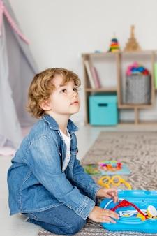 Vista lateral do menino brincando com brinquedos em casa