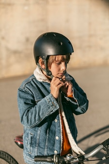 Vista lateral do menino colocando o capacete de segurança antes de andar de bicicleta