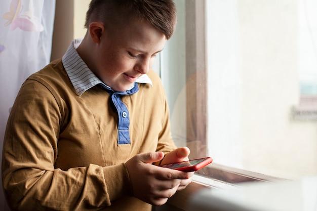 Vista lateral do menino com síndrome de down, segurando o smartphone