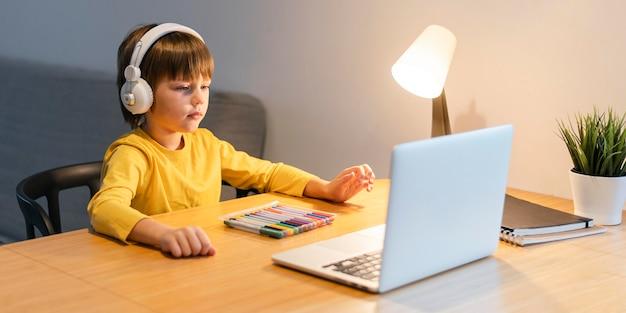 Vista lateral do menino da escola de camisa amarela tendo aulas virtuais