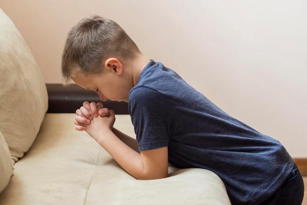 Vista lateral do menino rezando