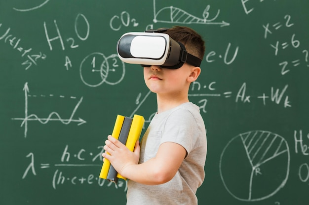 Vista lateral do menino usando fone de ouvido de realidade virtual e segurando livros