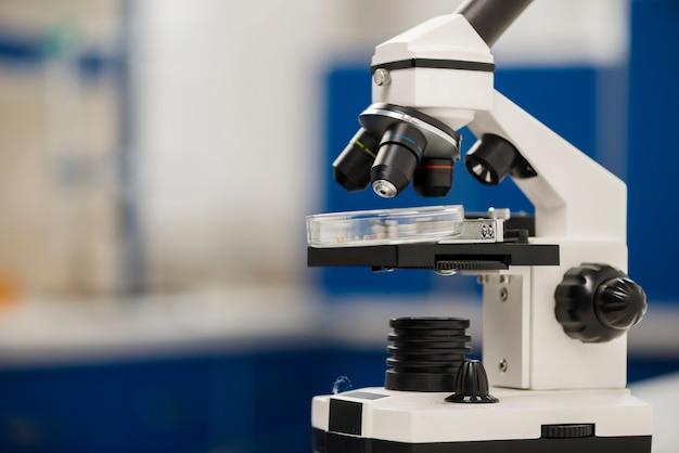 Vista lateral do microscópio no laboratório com espaço de cópia