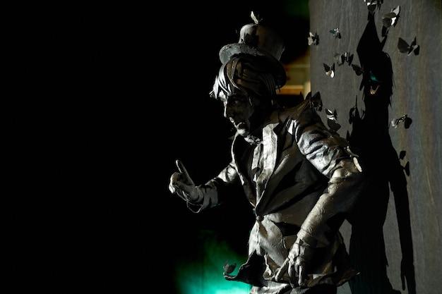 Vista lateral do mímico profissional mostrando emoções expressivas, vestido como uma estátua de bronze com muitas borboletas artificiais ao redor que parecem puxá-lo para o terno e o chapéu. artista masculino se apresentando no palco