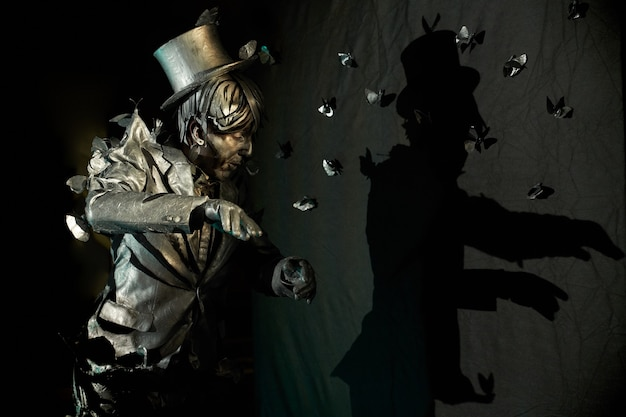 Vista lateral do mímico profissional mostrando emoções expressivas, vestido como uma estátua de bronze com muitas borboletas artificiais ao redor que parecem puxá-lo para o terno e o chapéu. conceito de ato de pantomima
