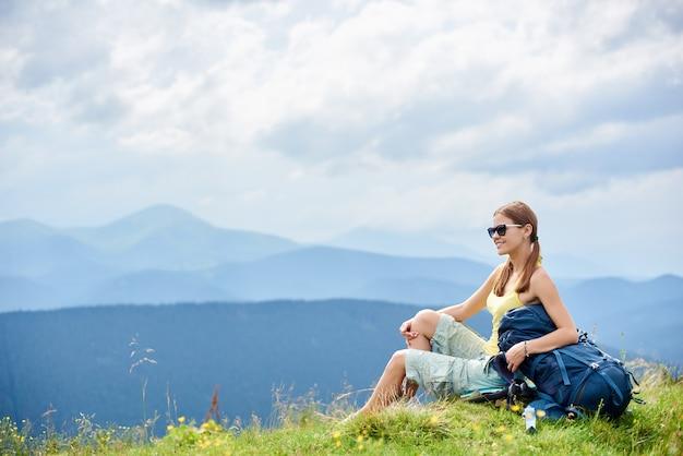 Vista lateral do mochileiro de mulher sentada na colina gramada com mochila, aproveitando o dia nublado de verão nas montanhas dos cárpatos