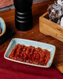 Vista lateral do molho de pimenta quente chamado adjika em um prato sobre uma mesa de madeira