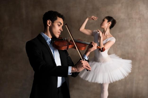 Vista lateral do músico masculino e bailarina