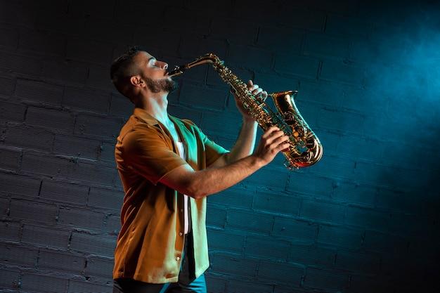 Vista lateral do músico tocando saxofone com espaço de cópia