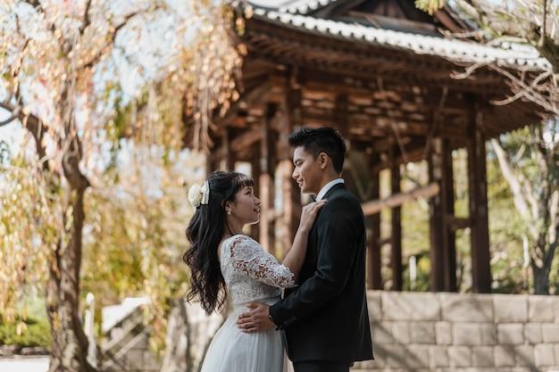 Vista lateral do noivo e da noiva abraçados ao ar livre