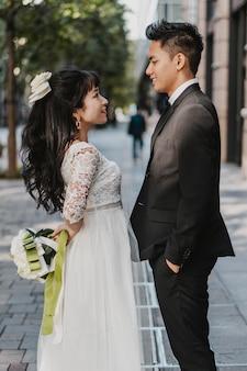Vista lateral do noivo e da noiva posando no meio da rua