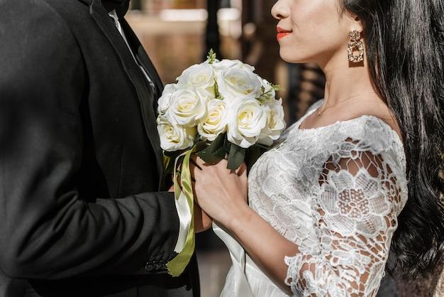 Vista lateral do noivo e da noiva segurando um buquê de flores