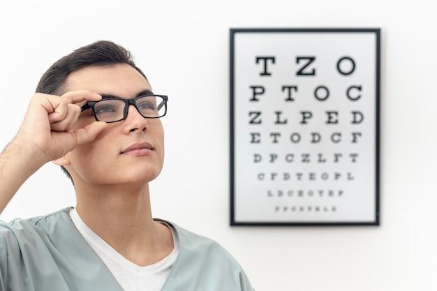 Vista lateral do oftalmologista tentando par de óculos