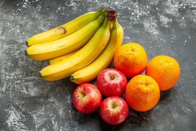 Vista lateral do pacote de bananas frescas de fonte de nutrição orgânica e maçãs vermelhas, uma laranja em fundo escuro