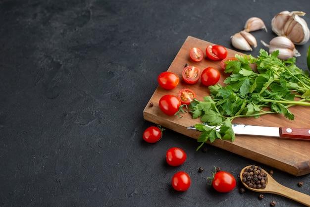 Vista lateral do pacote verde de tomates inteiros frescos cortados na tábua de madeira faca com alho e pimenta na superfície preta angustiada