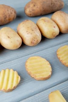 Vista lateral do padrão de batatas no fundo de madeira