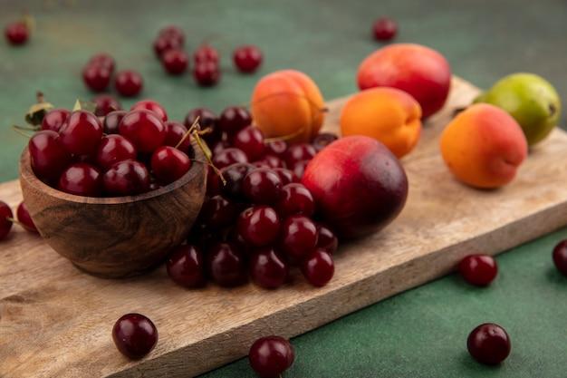 Vista lateral do padrão de frutas como damascos, pêssegos, peras, cerejas com tigela de cereja na tábua e sobre fundo verde