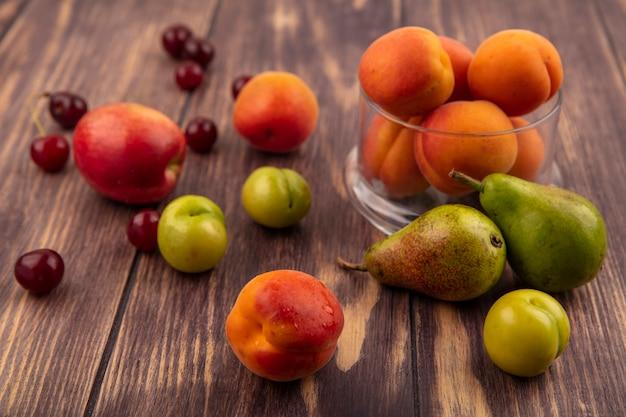 Vista lateral do padrão de frutas como pêssego, cerejas, ameixas, peras e pote de damascos no fundo de madeira