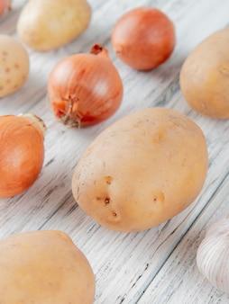 Vista lateral do padrão de legumes como cebola batata no fundo de madeira