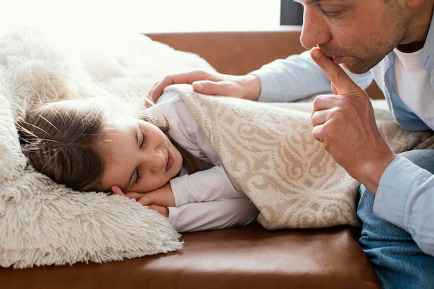Vista lateral do pai cobrindo a filha sonolenta com um cobertor e fazendo gestos silenciosos