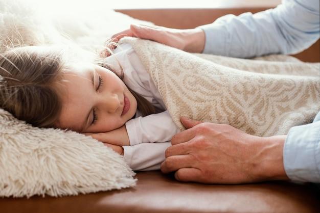 Vista lateral do pai cobrindo a filha sonolenta com um cobertor