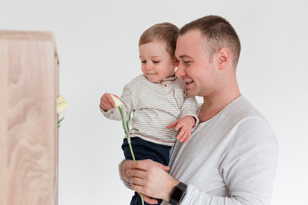 Vista lateral do pai com o filho segurando o pai