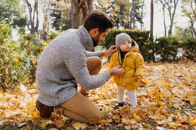 Vista lateral do pai passando um tempo com o bebê ao ar livre