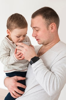 Vista lateral do pai segurando bebê