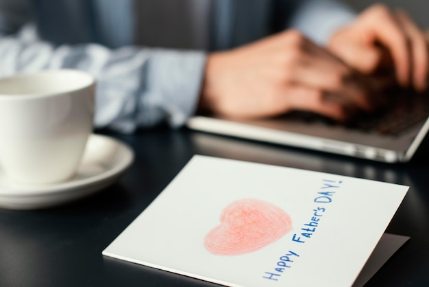 Vista lateral do pai trabalhando em um laptop com o cartão do dia do pai na mesa