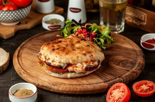 Vista lateral do pão árabe com carne e legumes na placa de madeira