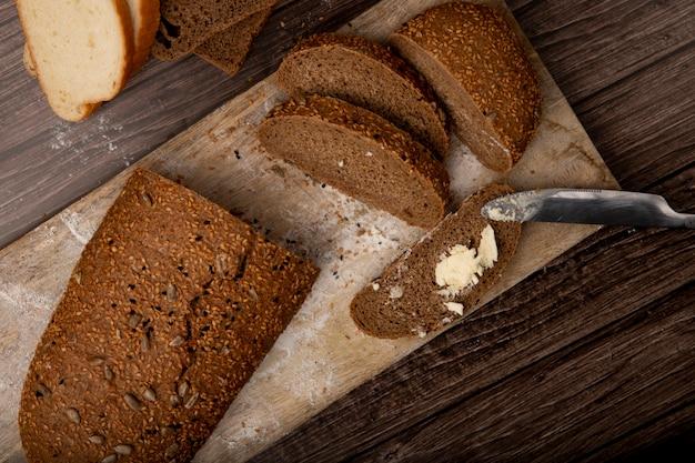 Vista lateral do pão de forma cortado e fatiado, pão com manteiga espalhe na fatia de pão com faca na placa de corte sobre fundo de madeira