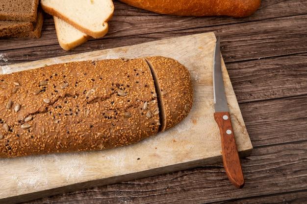 Vista lateral do pão de sanduíche cortado e faca na tábua no fundo de madeira