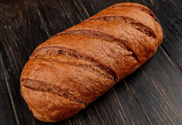Vista lateral do pão preto sobre fundo de madeira