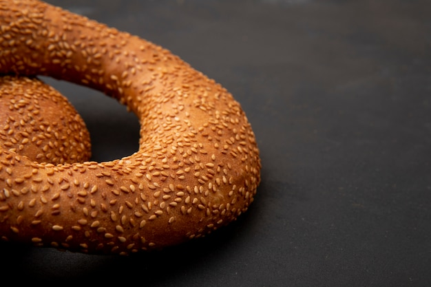 Vista lateral do pãozinho no lado esquerdo e fundo preto com espaço de cópia