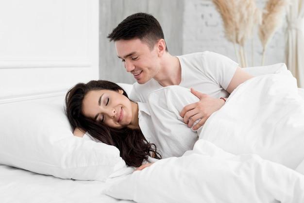 Vista lateral do par romântico na cama em casa
