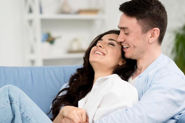 Vista lateral do par romântico no sofá em casa