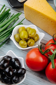 Vista lateral do pedaço de queijo holandês com cebola verde, azeitonas em conserva e tomates frescos na mesa de madeira cinza