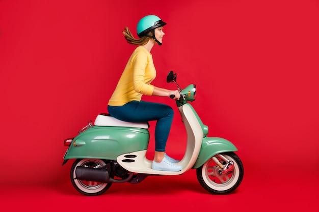 Vista lateral do perfil de uma adorável garota alegre dirigindo uma motocicleta em fundo vermelho