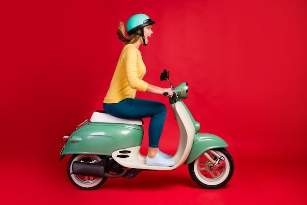 Vista lateral do perfil de uma garota alegre dirigindo uma motocicleta se divertindo na parede vermelha