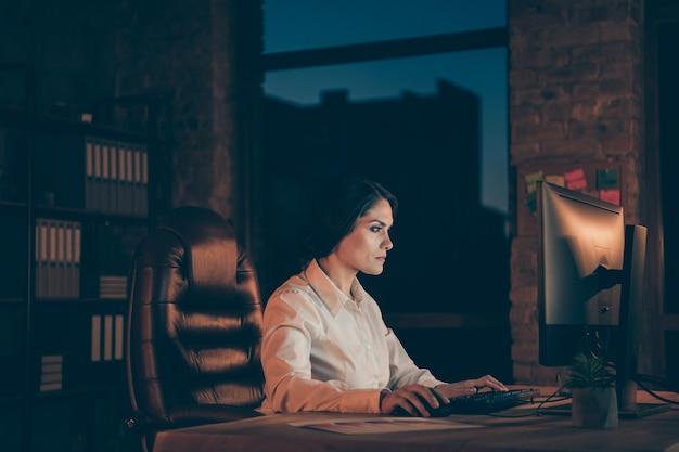 Vista lateral do perfil dela, ela é simpática, atraente, focada, trabalhadora, gerente, proprietário da empresa, digitando, criando uma nova rede de arquivos de inicialização de ti à noite escura estação de trabalho dentro de casa