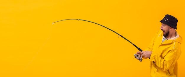 Vista lateral do pescador animado segurando a vara de pescar