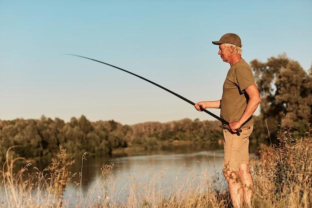 Vista lateral do pescador em pé na margem do lago ou rio e olhando para sua vara de pescar nas mãos, pescando no pôr do sol, na bela natureza, vestindo camiseta e calças verdes.
