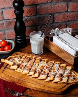 Vista lateral do pide turco com legumes carne e queijo, dispostos em uma tábua de madeira