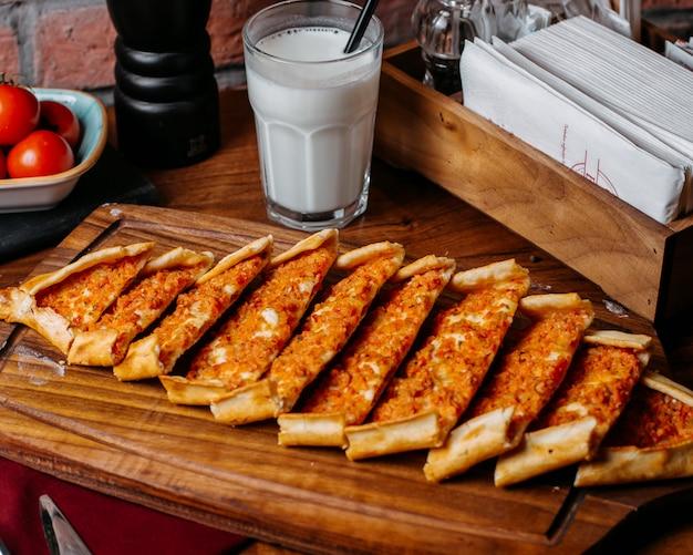 Vista lateral do pide turco com legumes e carne, dispostos sobre uma tábua de madeira