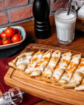 Vista lateral do pide turco com queijo, disposto em uma tábua de madeira